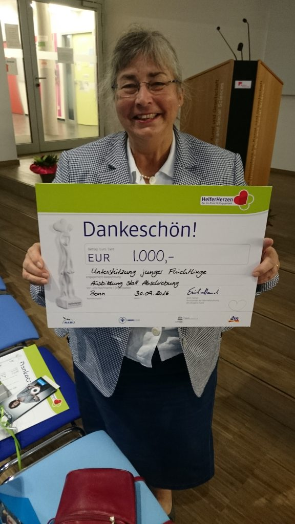 Camilla Heynen, Beisitzeron im Vorstand von AsA, präsentiert den Scheck der dm-Stiftung