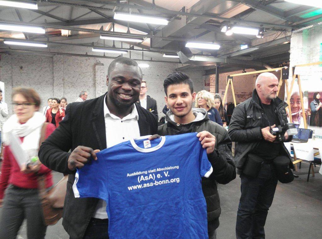 """Roni Hussain aus Syrien, 17 Jahre, überreicht unser ASA-Tshirt an Gerald Asamoah, der auf Schalke immer nur kurz """"Asa"""" gerufen wurde."""